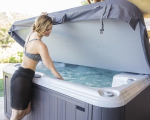 Woman opening up her outdoor hot tub.