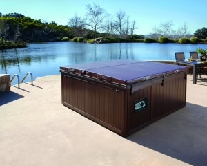 Outdoor hot tub with a cover on placed by the water.