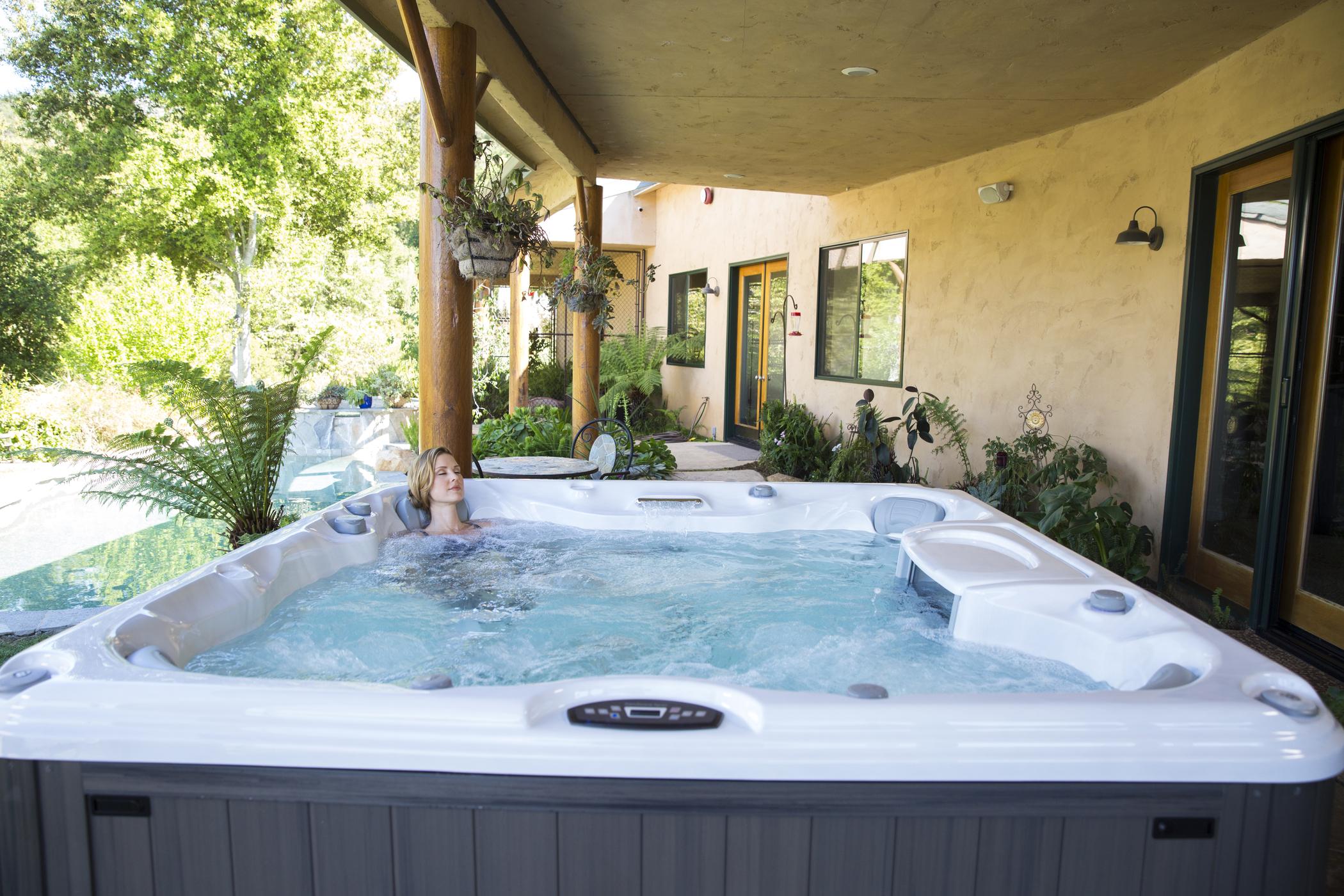 Woman soaking in a Sundance Spas hot tub.