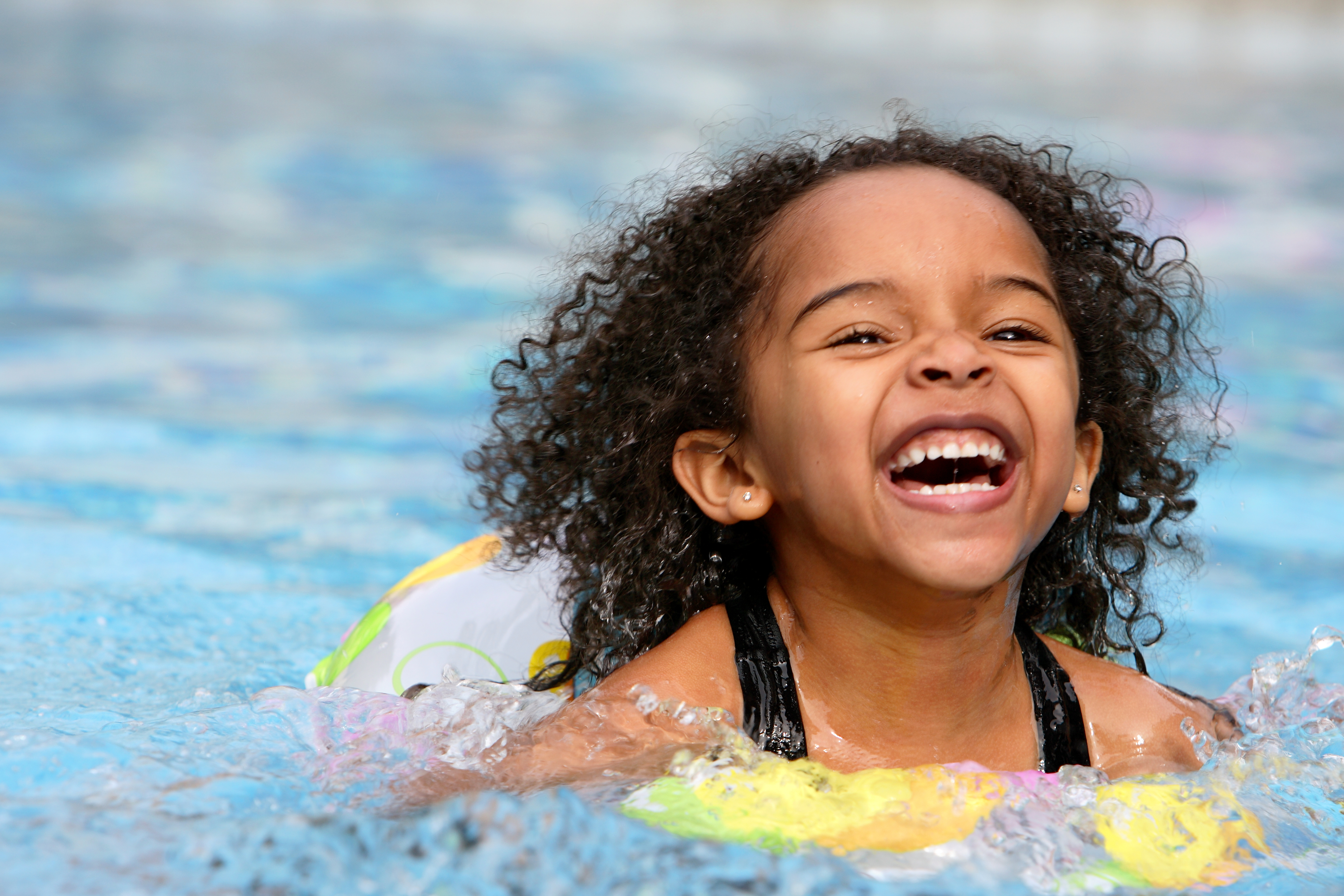 Little girl happily swimming.